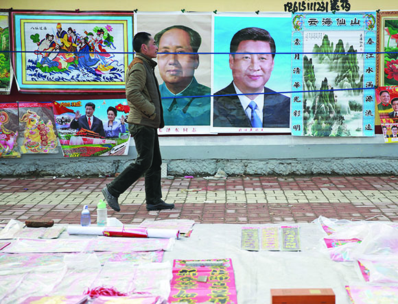 A man walks past New Year decoration pictures featuring China's President Xi Jinping, China's late Chairman Mao Zedong and some other current senior officials, at a market in Juancheng